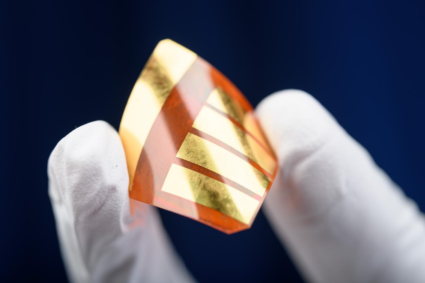 A researcher at Georgia Tech holds a perovskite-based solar cell, which is flexible and lighter than silicon-based versions.